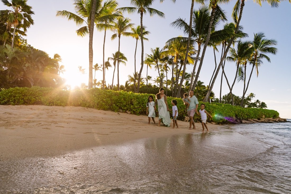 family walking on the beach in koolina at sunrise by Family Photographers on Oahu