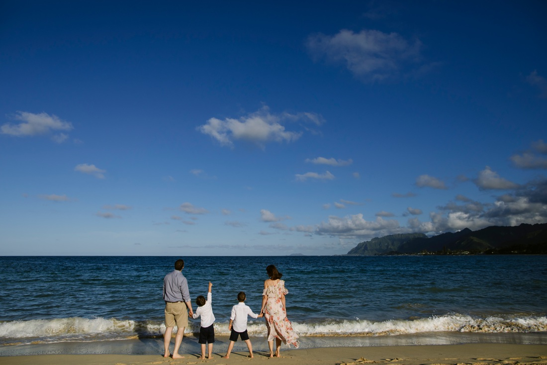 family playing at the edge of the ocean in oahu with mountain view in the distance