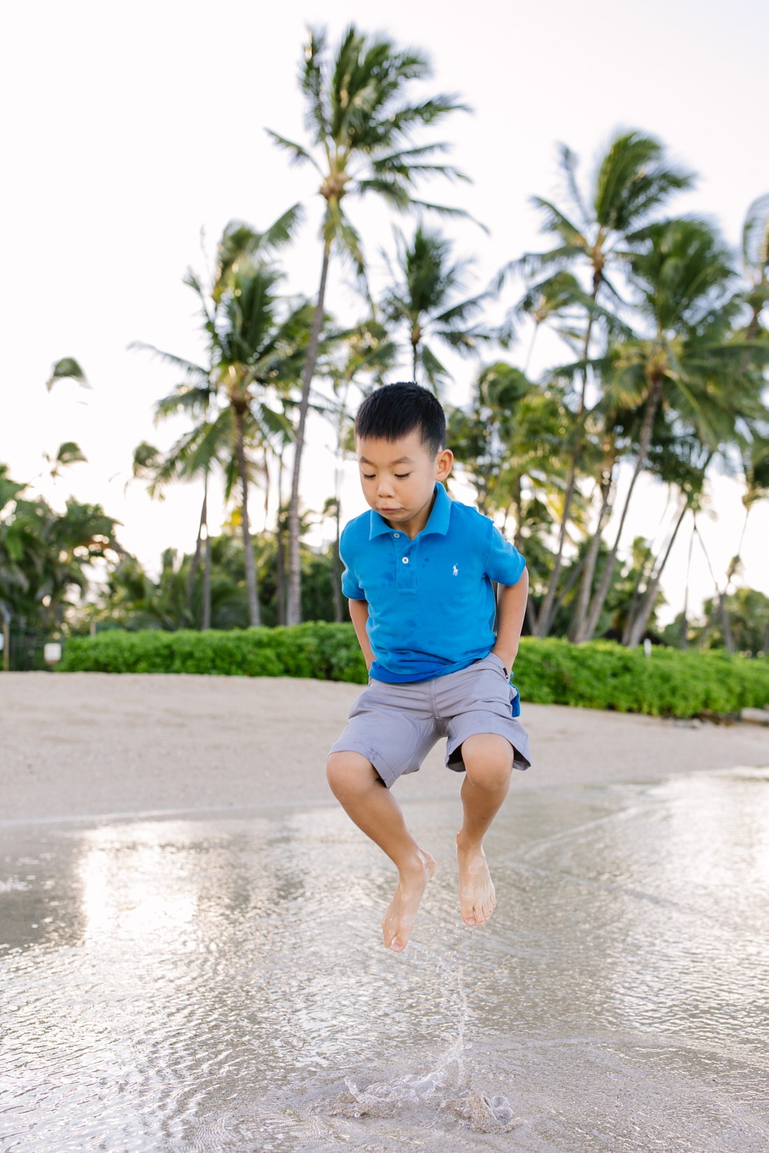 boy jumping in the shallows during a family photoshoot in oahu