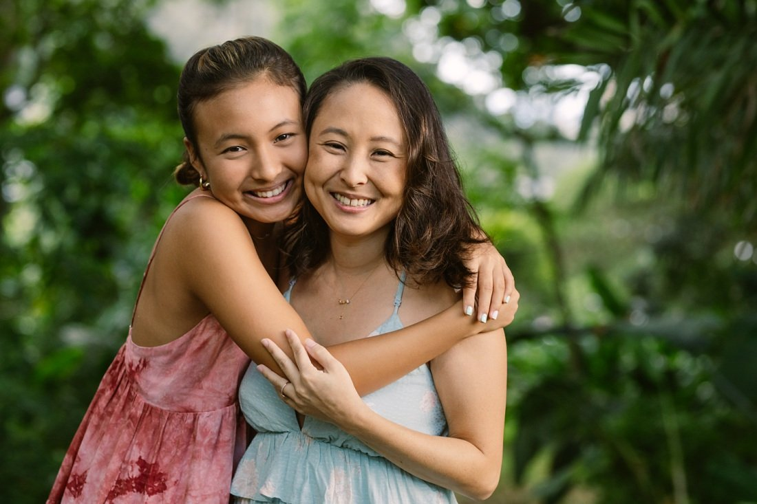 portrait of mom and teenage daughter hugging during oahu family photoshoot