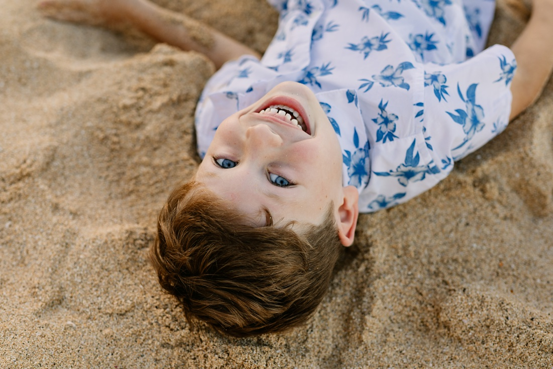 portrait of a boy lying in the sand