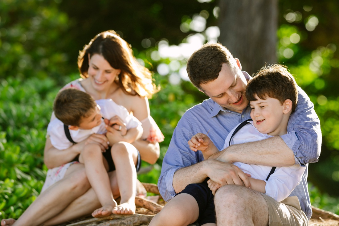family snuggling for family portraits at laie beach park in hawaii
