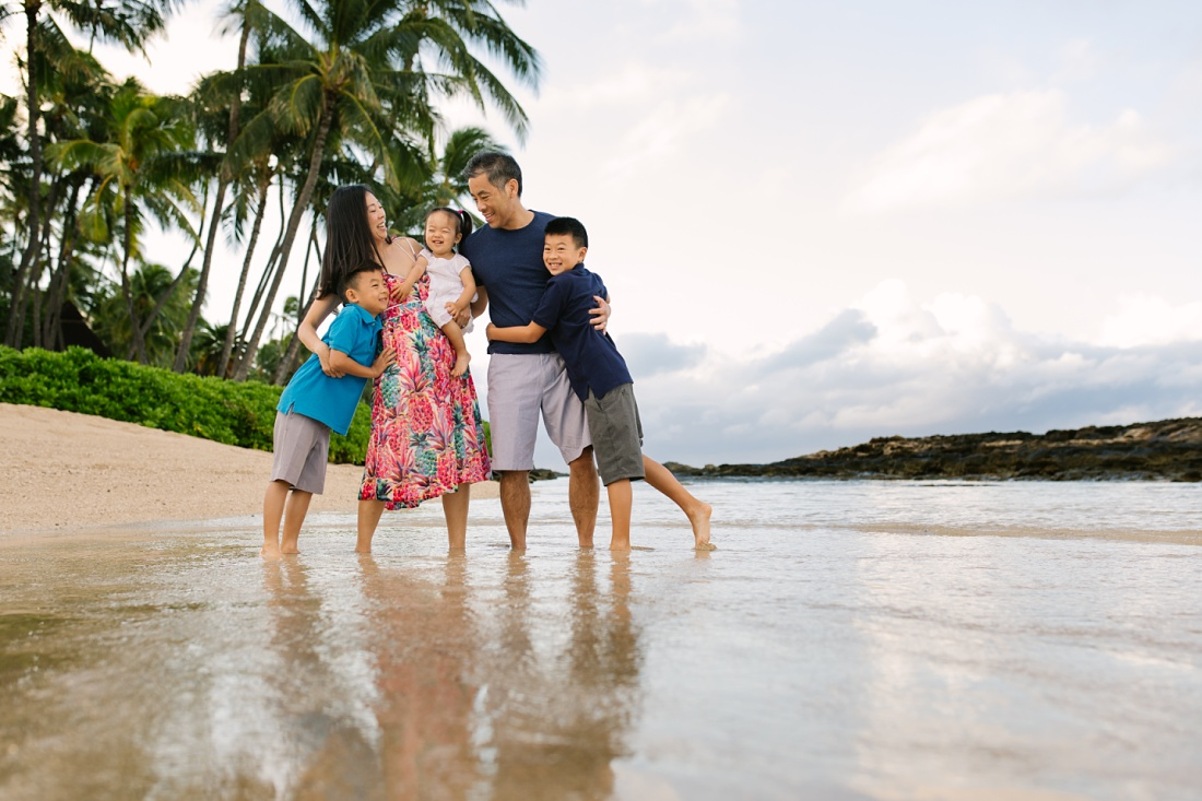 Family hug at paradise cove beach during a family photo session in hawaii