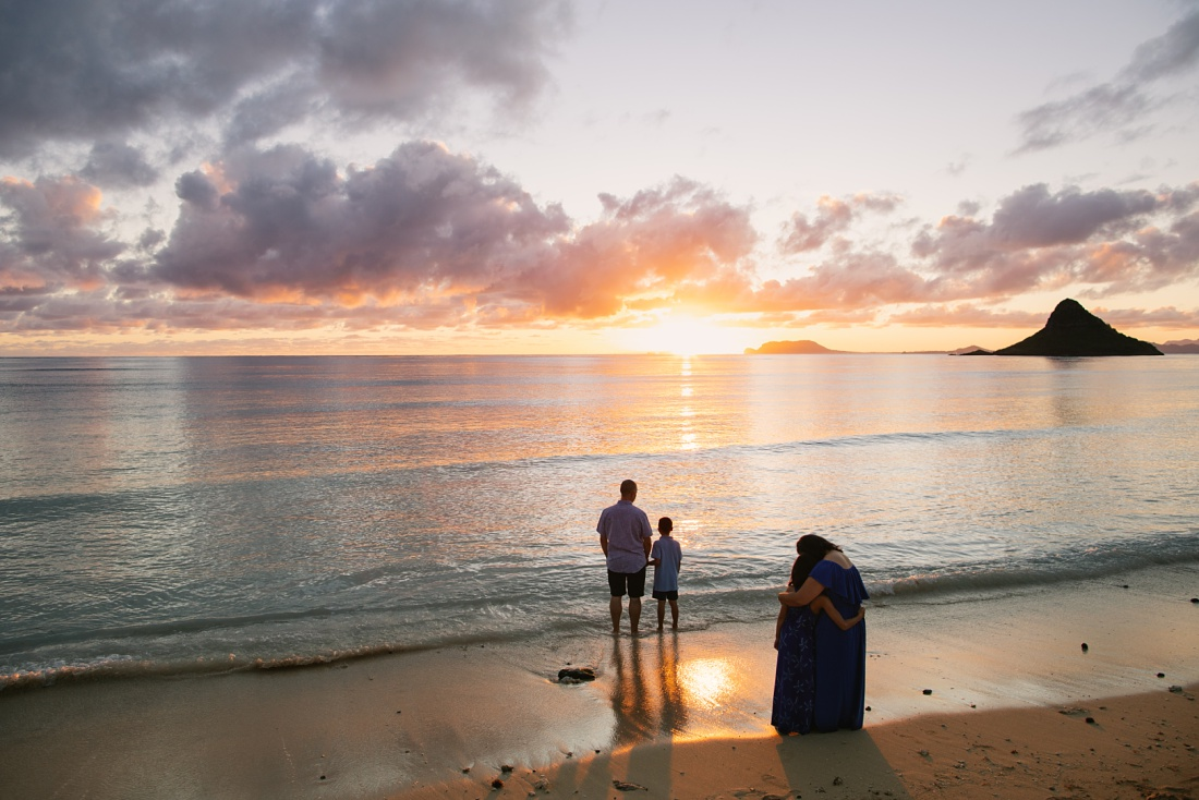 family watching the sun rise over the beach during Sunrise Family Portraits on Oahu