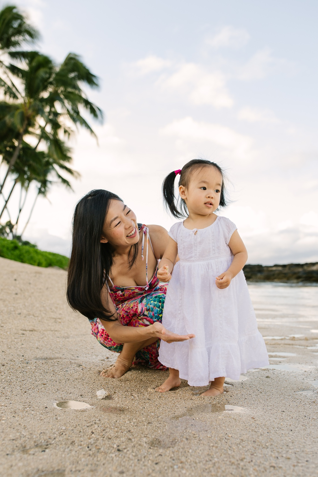 mom and toddler daughter portrait of her first time at the beach in hawaii