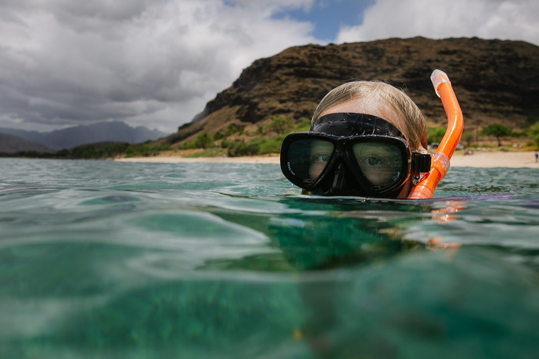 closeup of girl snorkeling at electric beach in oahu, hawaii