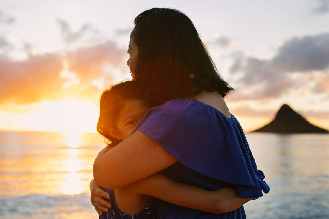 mom and daughter hug at sunrise in oahu during a beach photoshoot by little bird photography