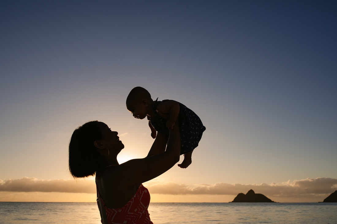 silhouette of mom holding baby in the air at sunrise on lanikai beach