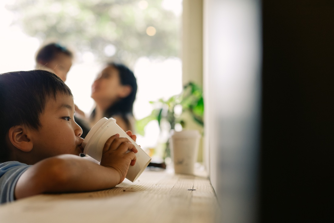 boy sipping hot chocolate during a hawaii lifestyle photography session