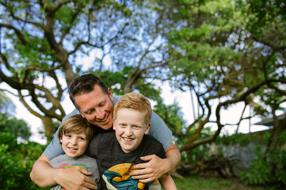 dad hugging his sons at kalama beach park in kailua during a family photoshoot