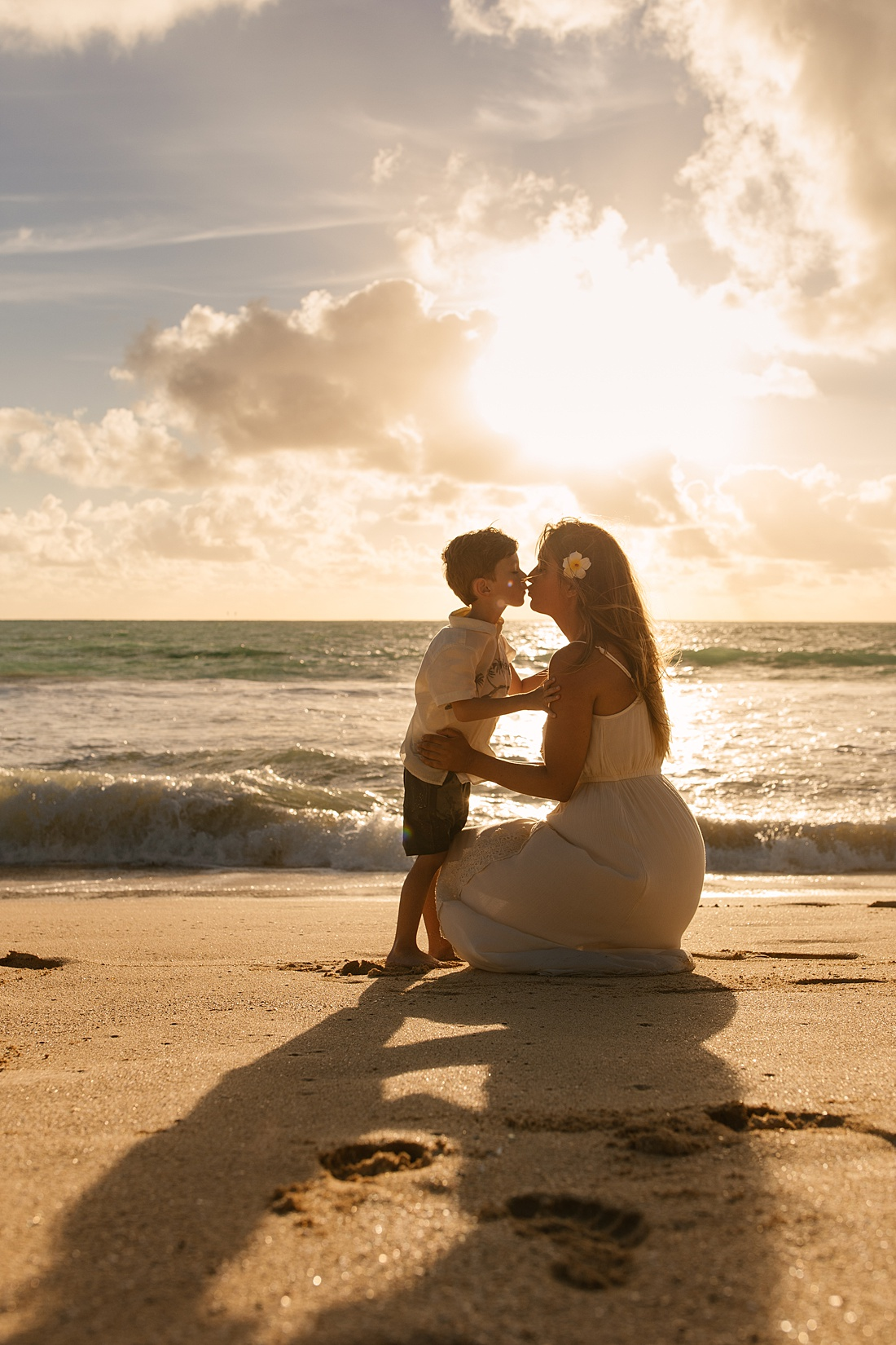 mom and son kiss during a sweet Oahu family photo shoot