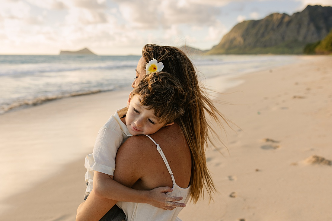 mom and son cuddle during a family photo session in hawaii