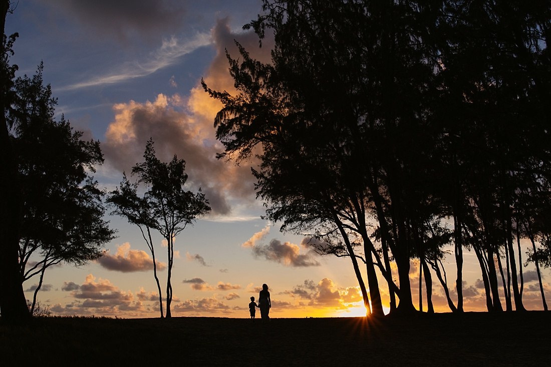mom and son walking towards the ocean at Sunrise in hawaii