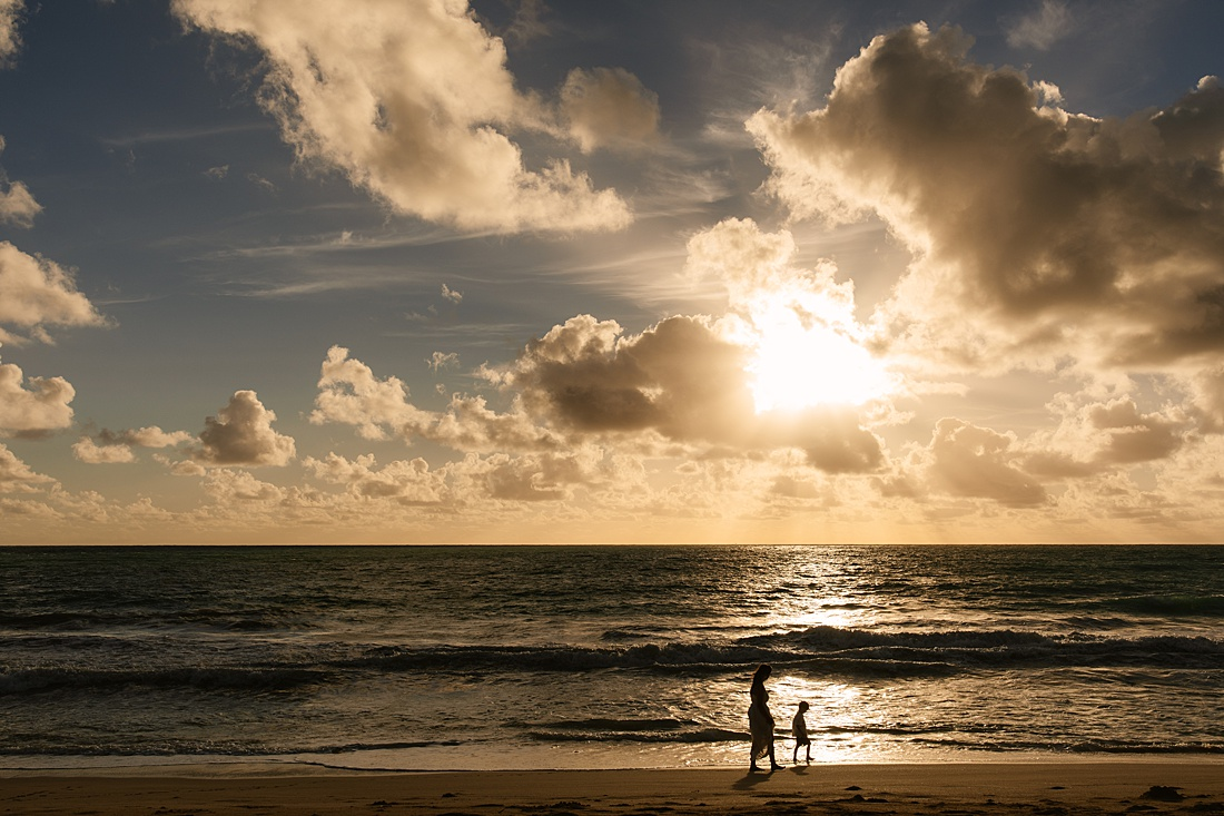 silhouettes of mom and son walking on Waimanalo Beach at sunrise