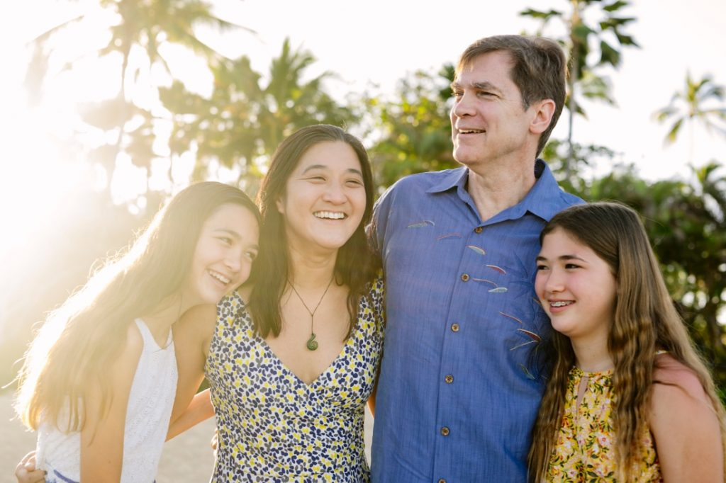 portrait of a happy family with palm trees and sun flare in hawaii