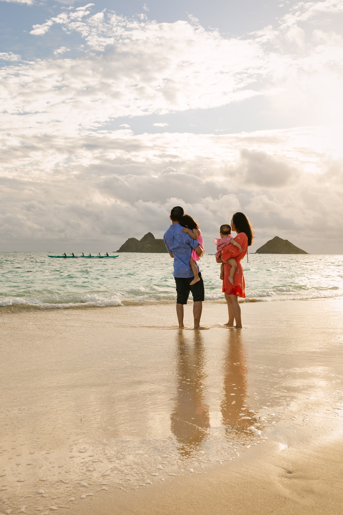 family watches outrigger off the mokulua islands at lanikai beach