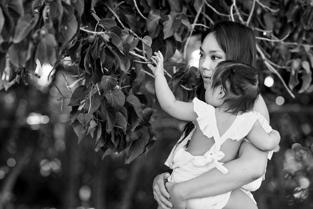 b&w photo of mom and baby looking for flowers in hawaii