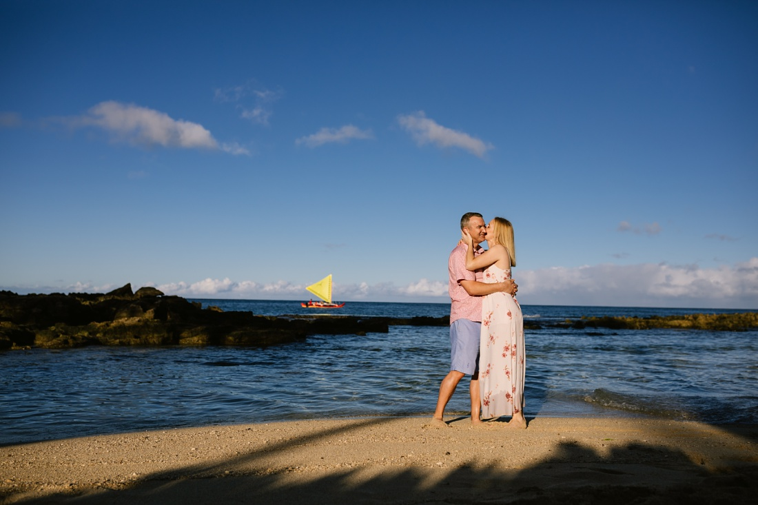couple portrait in hawaii with outrigger in the distance
