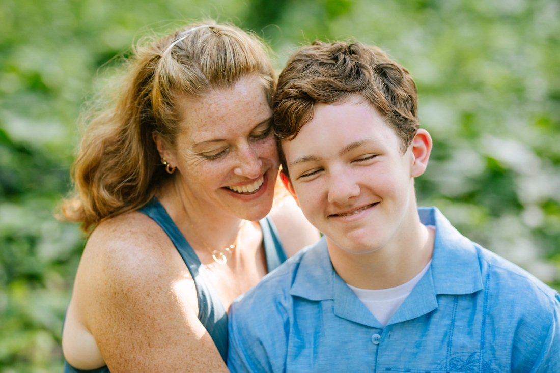 mom and teenage son share a moment during a family photo session in hawaii