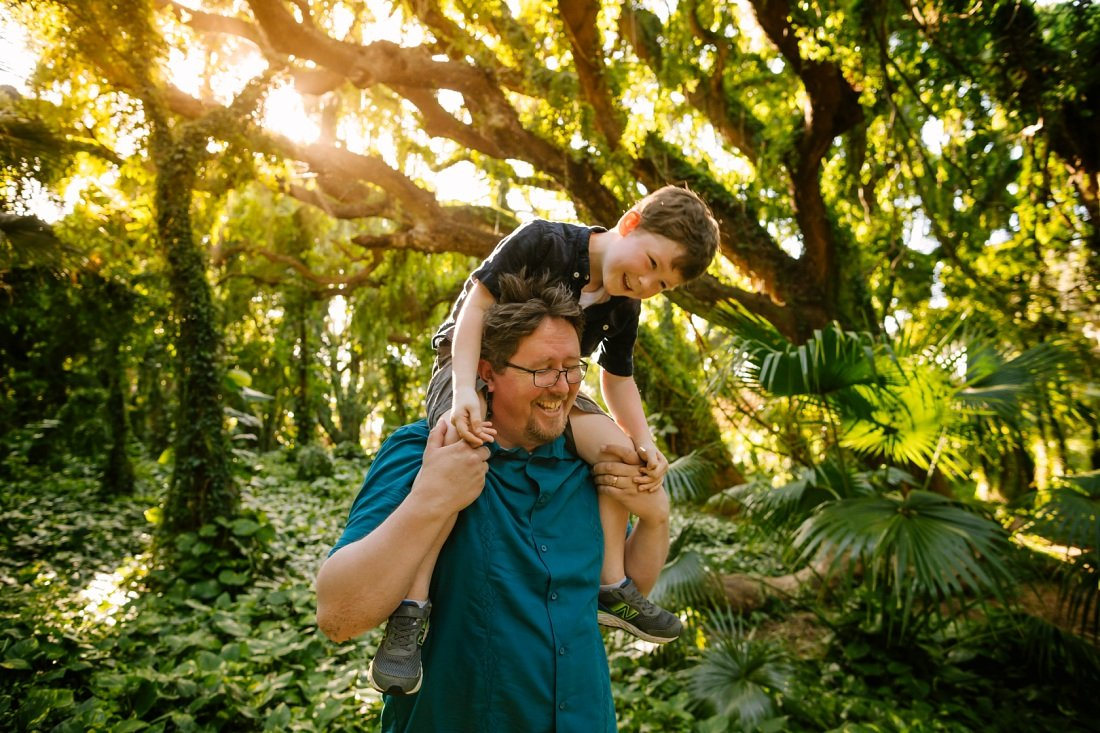 dad carries son on his shoulders in a Maui rainforest during a family photoshoot
