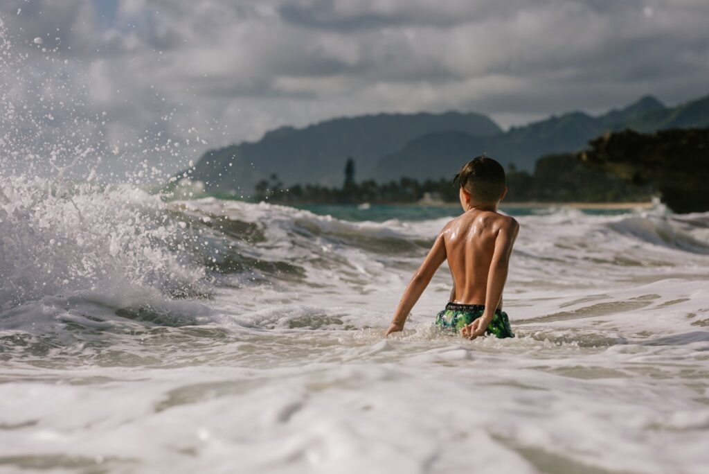 little boy at pounders beach in laie oahu during a family photo session