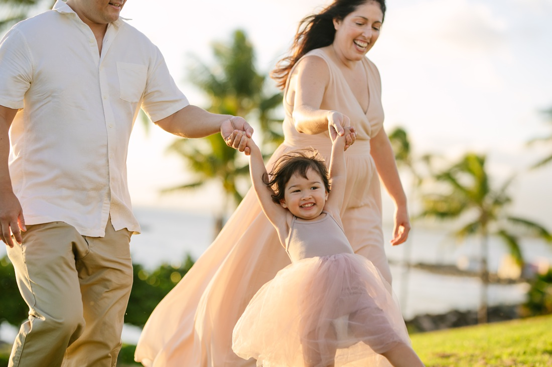 family swinging a toddler girl during a photo shoot at kakaako park