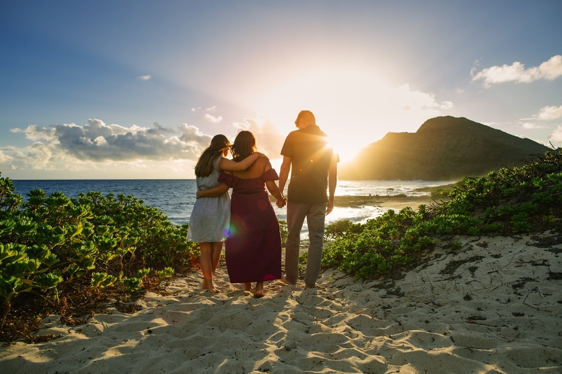 family walking on the beach at sunrise in oahu