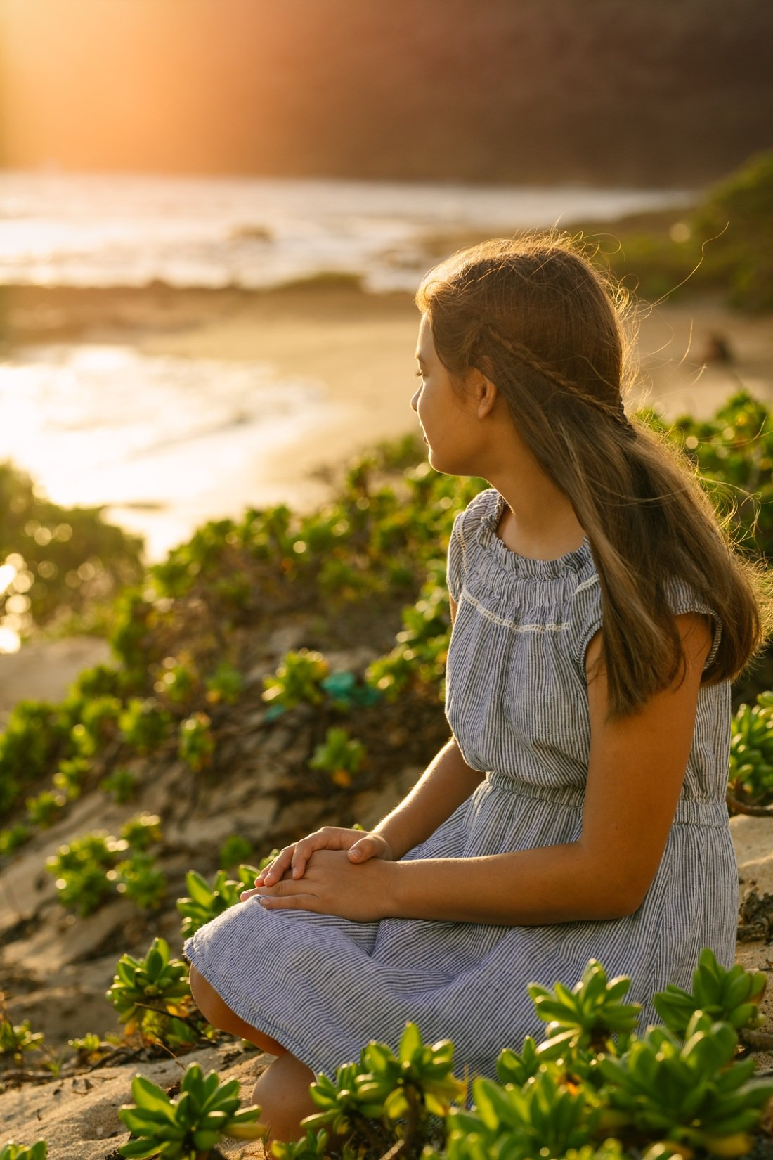portrait of a girl sitting on the dunes at sunrise oahu hawaii