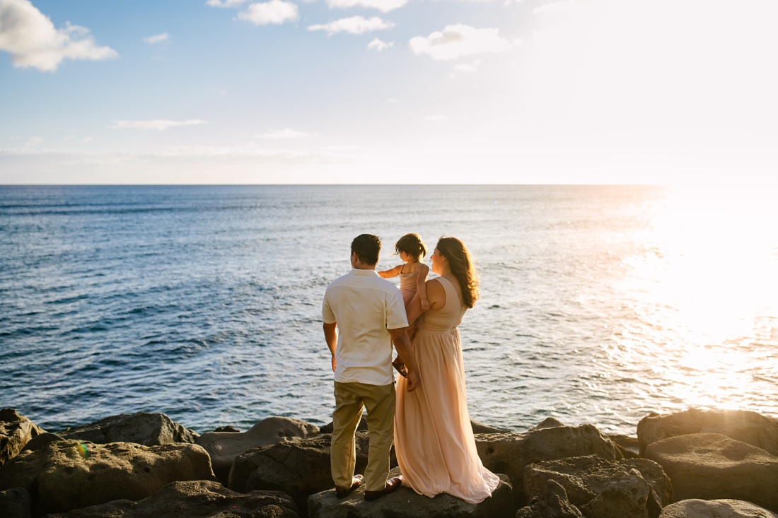 family of three at the kakaako waterfront park at sunset