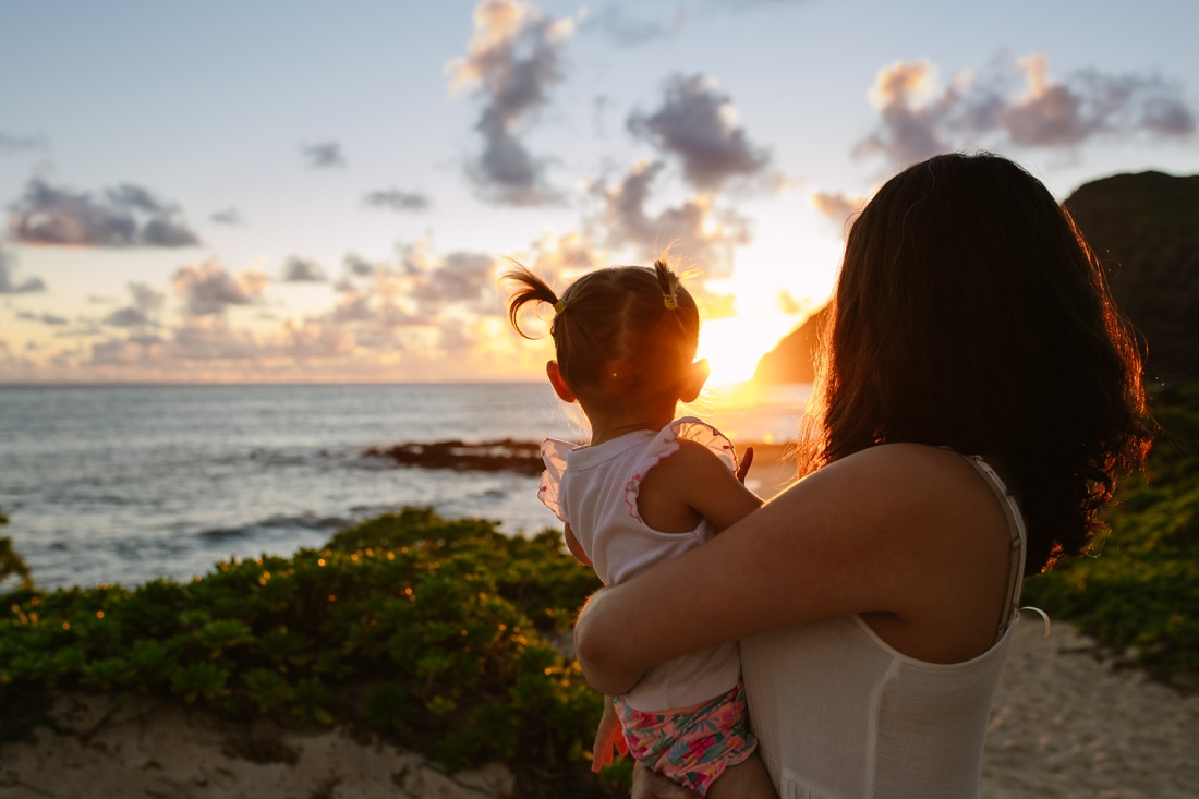 mom and toddler daughter watch sunrise in hawaii during a family photo session by little bird photography