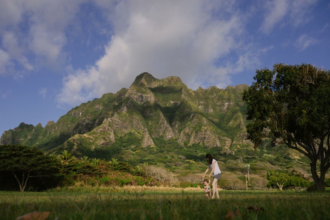 mom walks baby daughter with mountains behind at kualoa beach park oahu