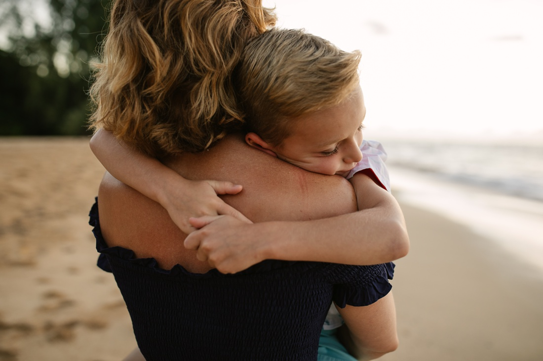 little boy hugging his mom during a family beach photoshoot
