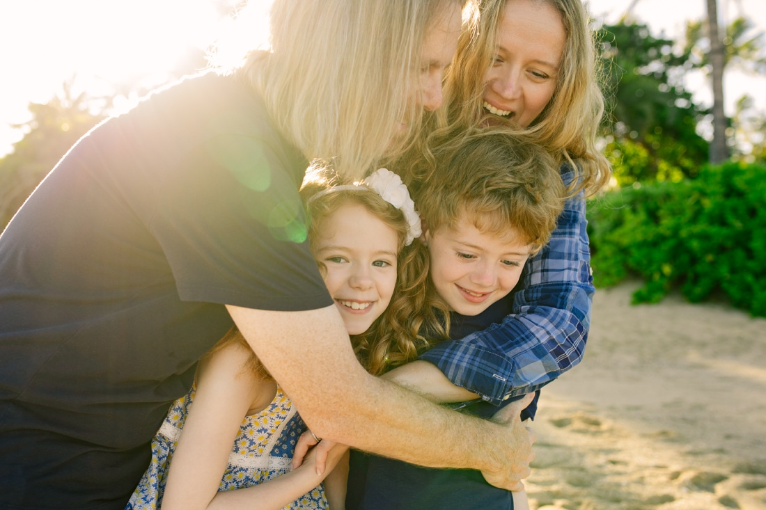 big family hug during a family portrait session at paradise cove beach in oahu