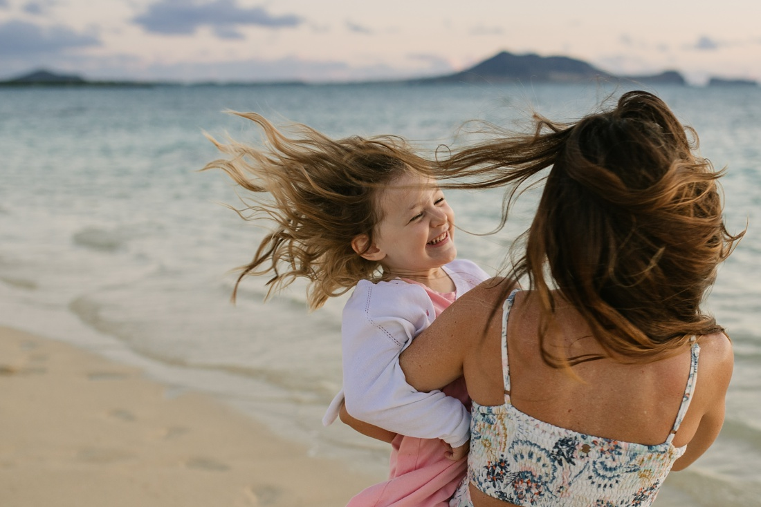 mom and daughter spinning on the beach in hawaii