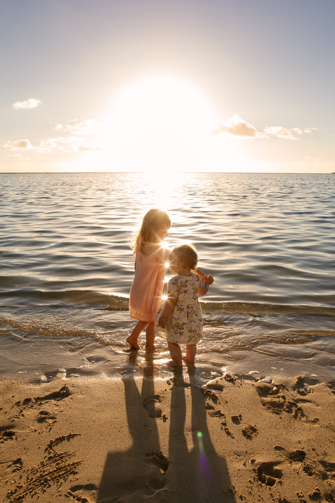 sisters dancing at lanikai beach during a sunrise family photo session