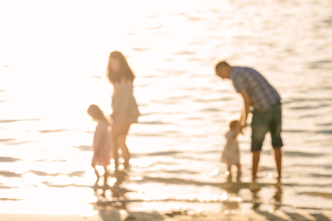 family out of focus in shimmering light of sunrise