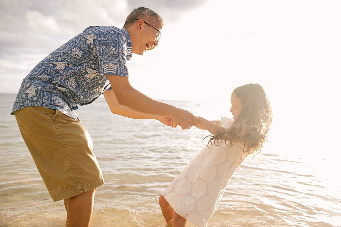 dad and daughter playing during a fun family portrait session at the beach in hawaii