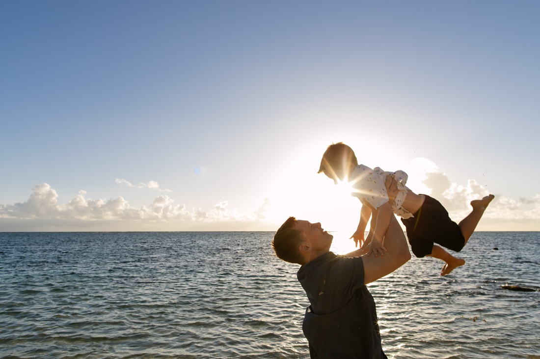 dad holding son in the air at sunrise at lanikai beach during a family portrait session