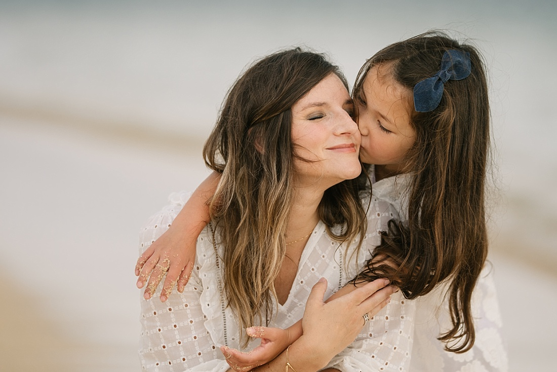 mom and daughter snuggle during a hawaii photo session