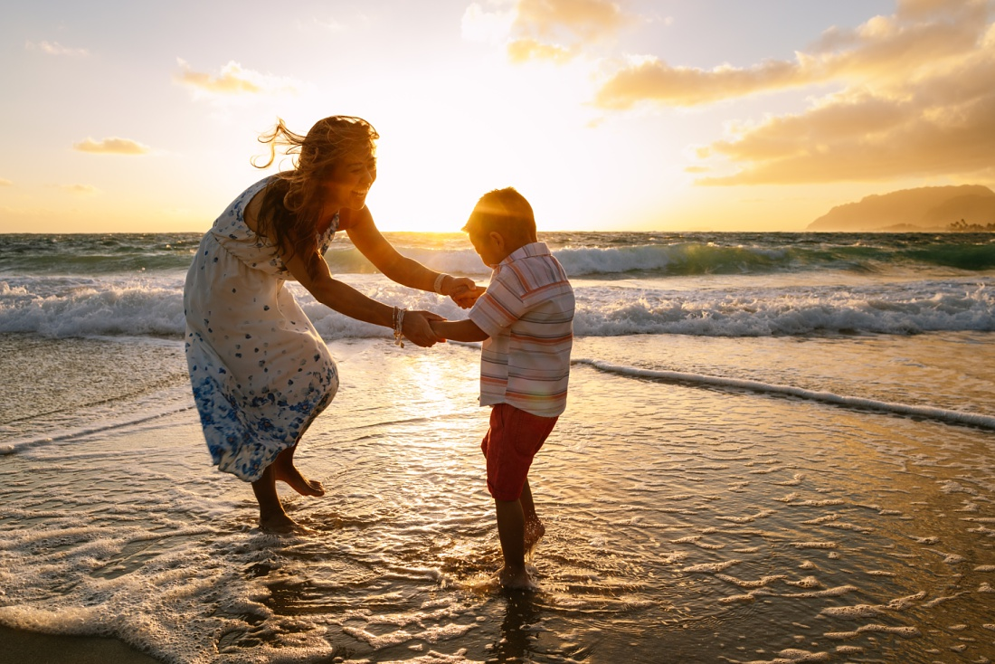 mom and son dance in the waves at sunrise in hawaii during a Fun Family Photography Session