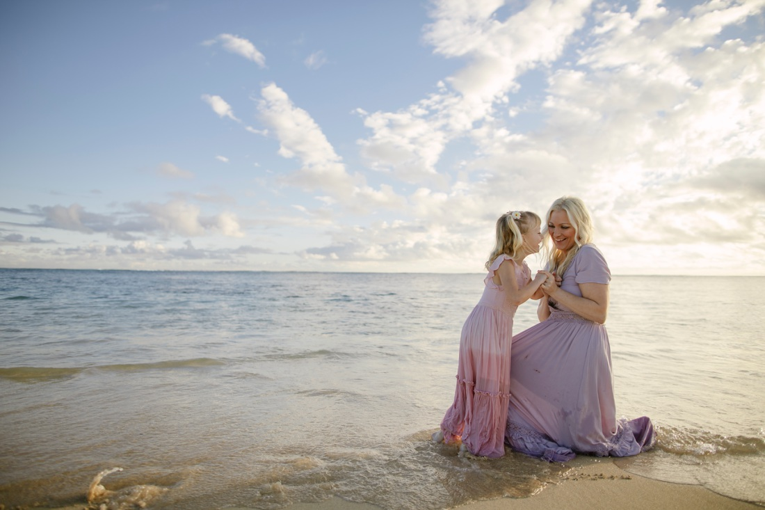 mom and daughter sharing a laugh on the beach in hawaii at sunrise