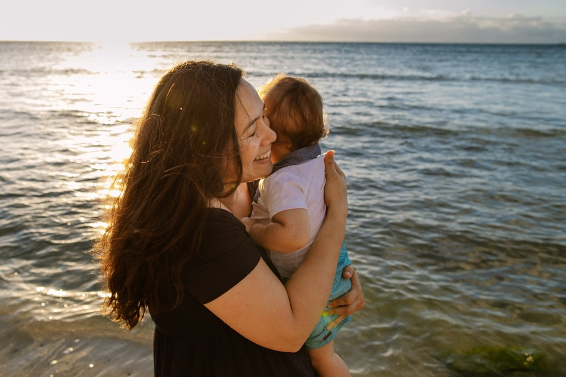 mom hugs baby tightly during a sunrise photo session in oahu