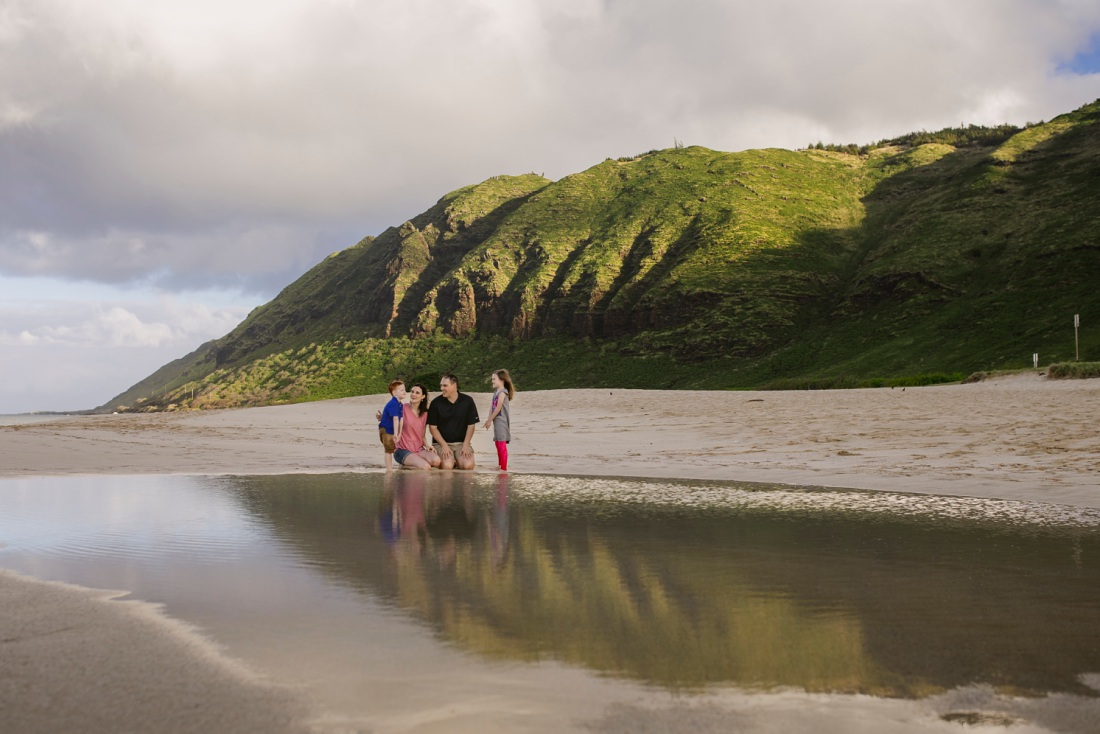 family sitting on the beach with reflections of mountains at yokohama bay oahu