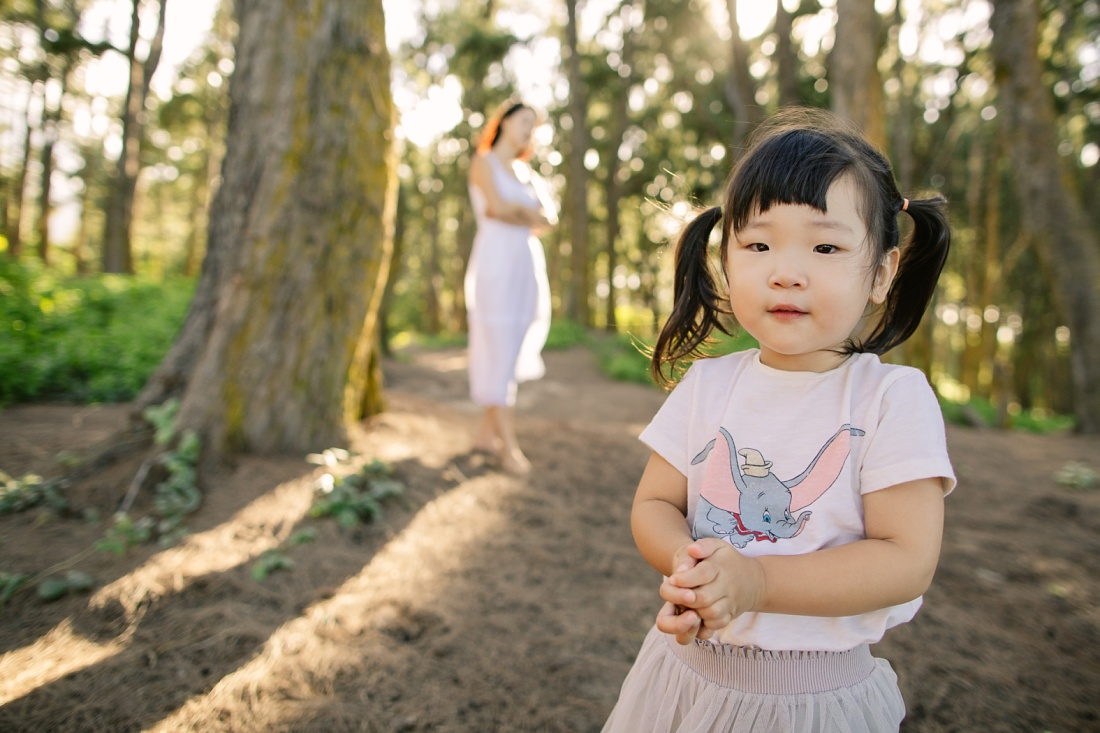 toddler girl in the forest with mom in the background by little bird photography