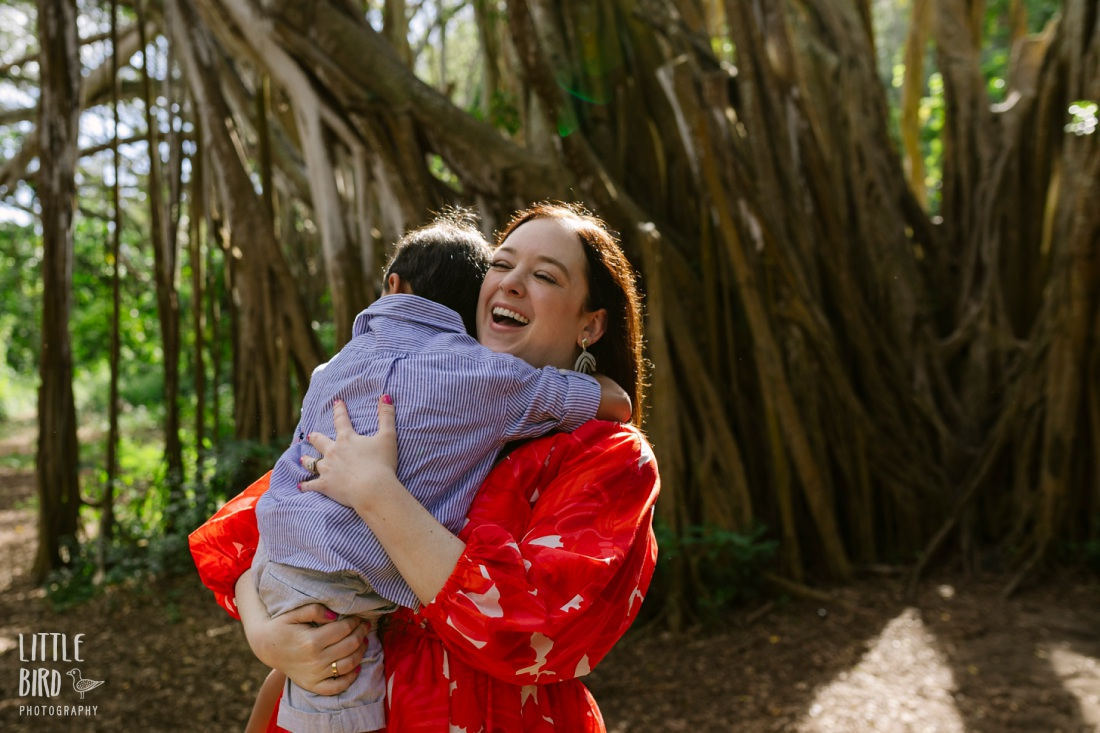 mom laughing while hugging son during a fun family photo session in hawaii