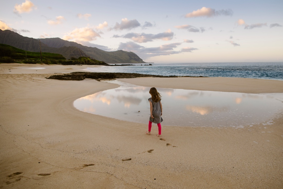 girl walking on the beach with clouds reflecting in a shallow pool and mountains in the background