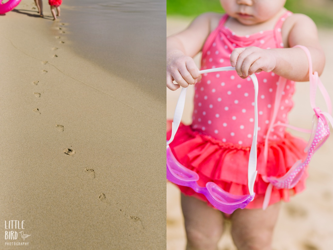 toddler in pink swimsuit playing at the beach during a lifestyle family photo session