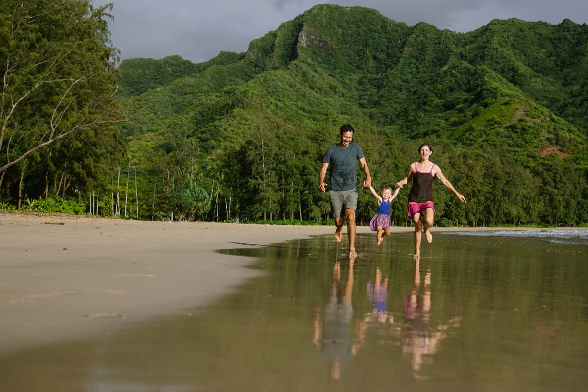family running on Kahana Beach with mountains behind and reflections