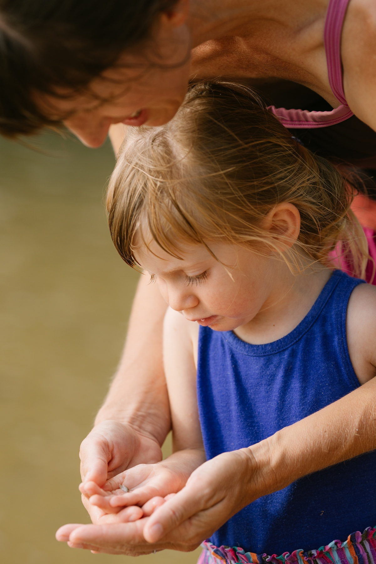 mom showing toddler daughter a tiny fish during a family adventure photography session
