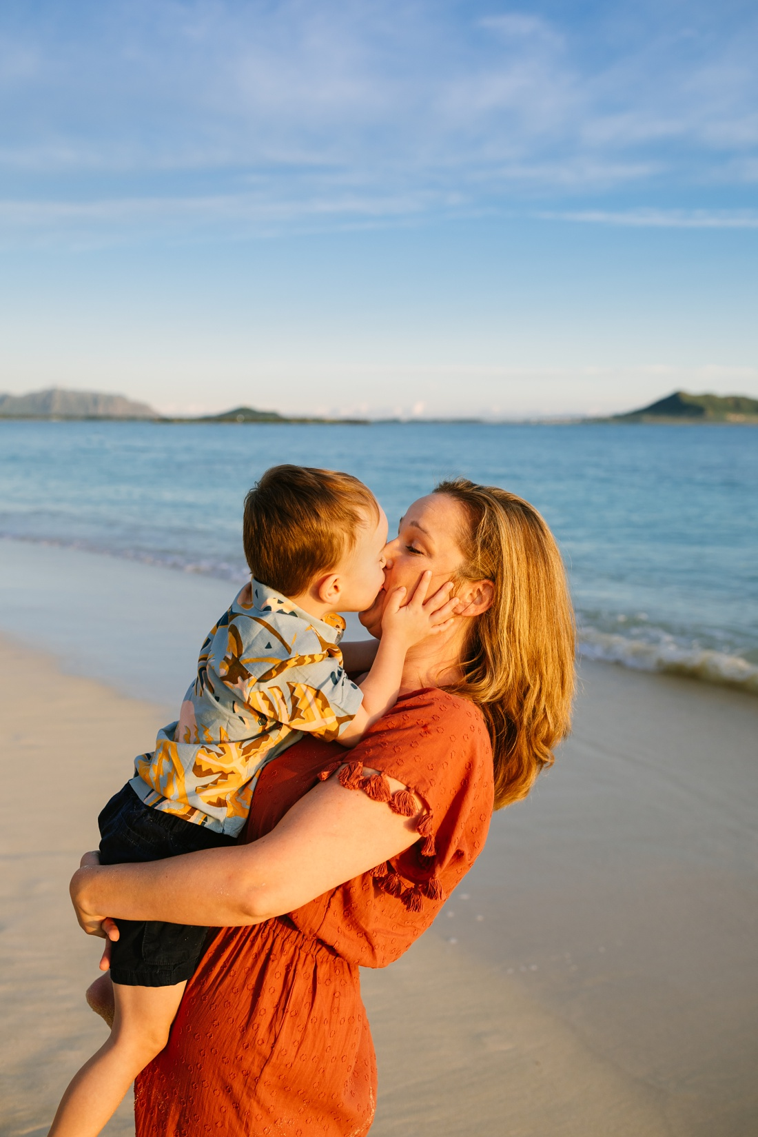boy surprises mom with a big kiss during a sunrise photo session in hawaii